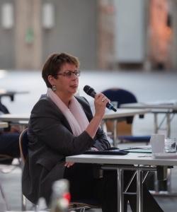 Ministerin Hone mit Mikrophon befragt das Projektteam